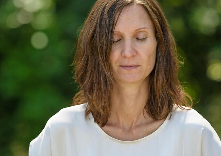 Tina Klein bei der Meditation auf einer Wiese