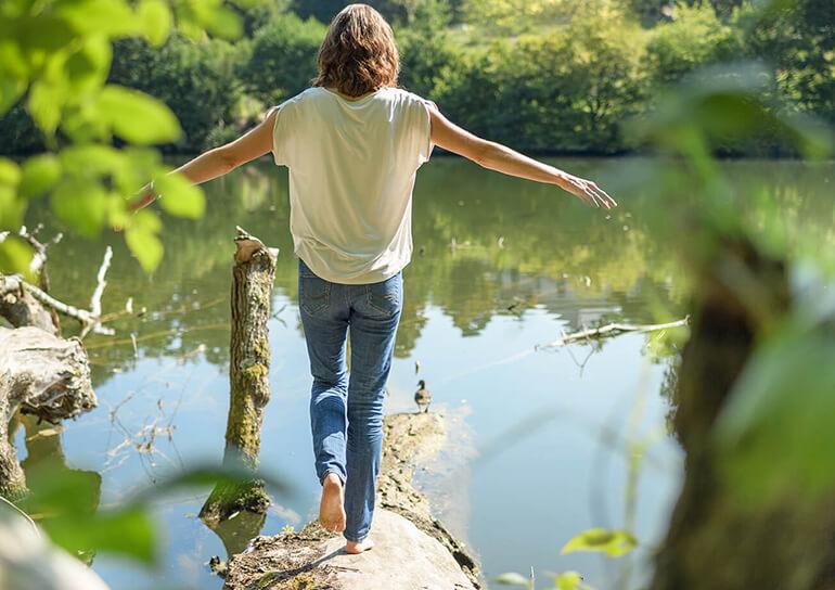 Tina Klein Balance auf einem liegeden Baumstumpf